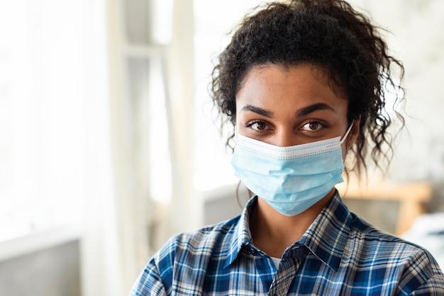Vista frontal de la mujer con máscara médica y espacio de copia