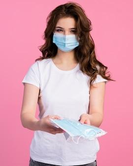 Vista frontal de la mujer con máscara médica que ofrece otras máscaras