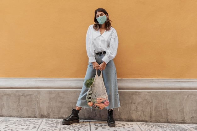 Vista frontal de la mujer con mascarilla y bolsas de la compra fuera
