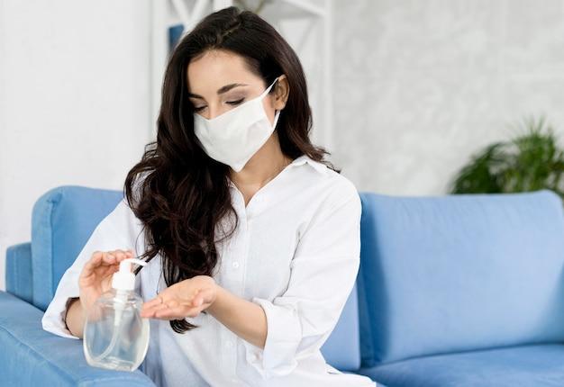 Vista frontal de la mujer con mascarilla desinfectando su mano