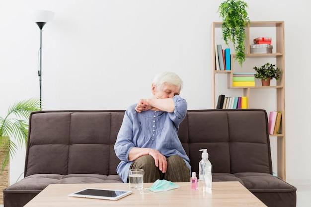 Vista frontal de la mujer mayor en casa tosiendo en el codo