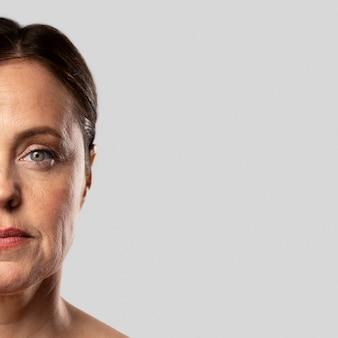 Vista frontal de la mujer mayor posando estoica con maquillaje y espacio de copia