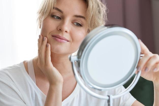 Vista frontal mujer mirando en el espejo