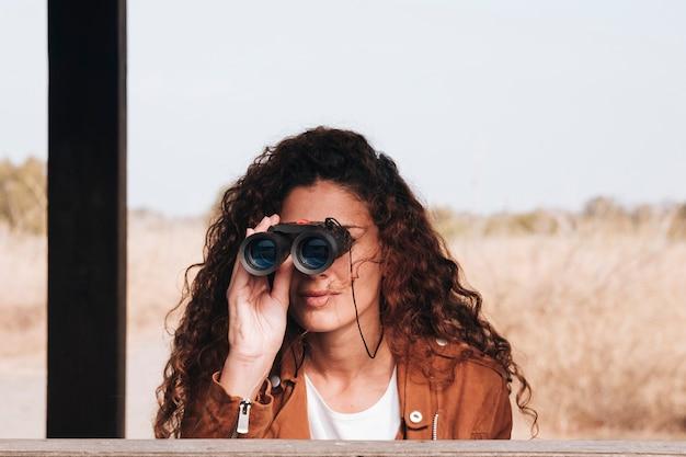 Vista frontal mujer mirando a través de binoculares