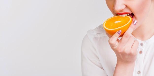 Vista frontal de la mujer mordiendo una naranja