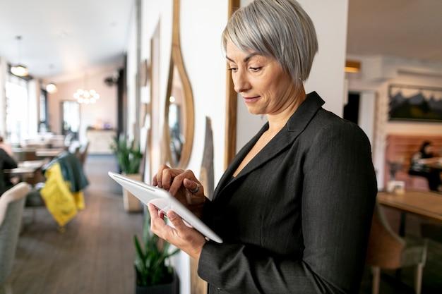 Vista frontal, mujer de negocios, lectura, de, tableta