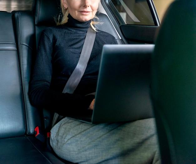 Vista frontal de la mujer de negocios mayor que trabaja en la computadora portátil en el cuidado