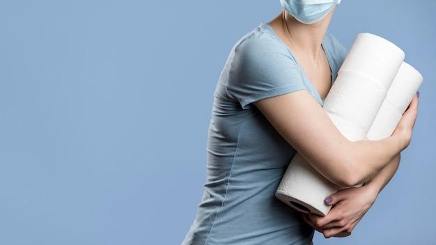 Vista frontal de la mujer oculta rollos de papel higiénico mientras llevaba máscara médica