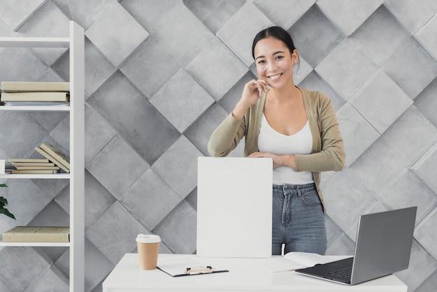 Vista frontal mujer en la oficina hablando por teléfono