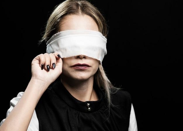 Vista frontal de la mujer con los ojos vendados
