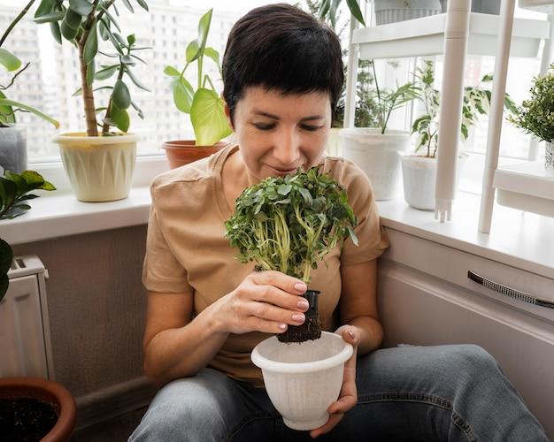 Vista frontal, de, mujer, oler, planta interior