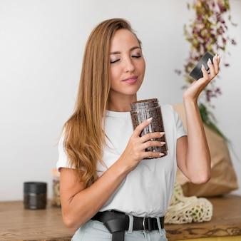 Vista frontal mujer oliendo granos de café