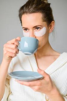 Vista frontal de la mujer con parches en los ojos tomando café