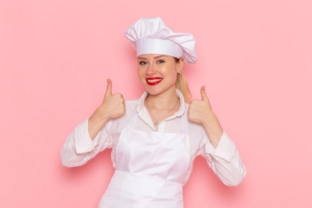 Vista frontal mujer pastelera en ropa blanca sonriendo y posando en la pared rosa cocinar confitería trabajo de pastelería dulce
