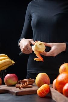 Vista frontal mujer pelando manzana fresca con cuchillo en la mesa de la cocina