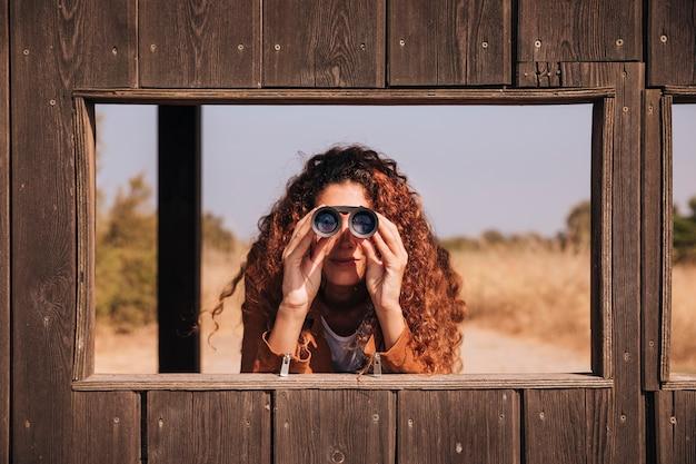 Vista frontal mujer pelirroja mirando a través de binoculares