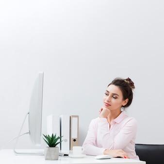 Vista frontal de la mujer pensativa en su escritorio mirando la computadora