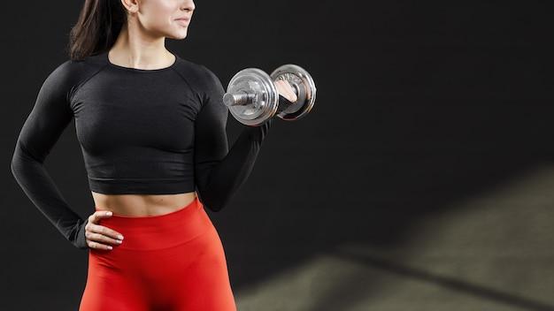 Vista frontal de la mujer con pesas y copia espacio