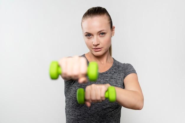 Vista frontal de la mujer con pesas de fisioterapia