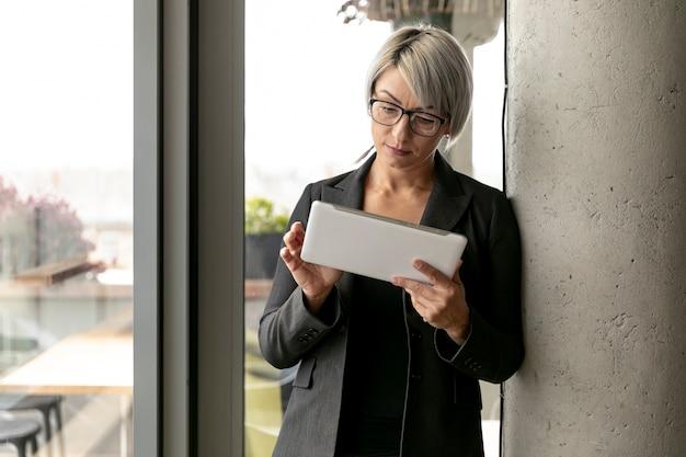 Vista frontal mujer de pie y sosteniendo la tableta