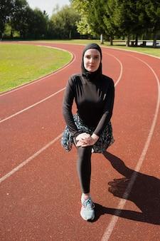Vista frontal de la mujer en la pista de atletismo