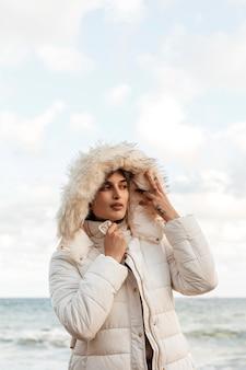 Vista frontal de la mujer en la playa con chaqueta de invierno y espacio de copia