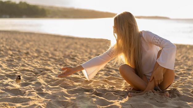 Vista frontal de la mujer en la playa con pájaro