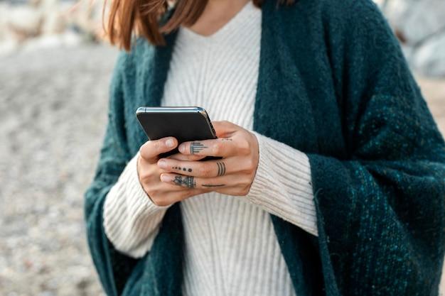 Vista frontal de la mujer en la playa con smartphone