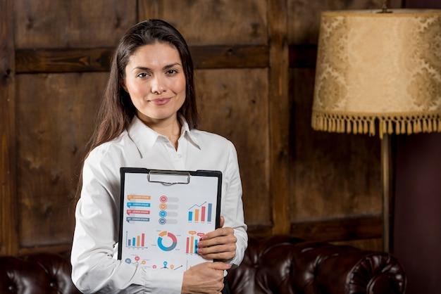 Vista frontal mujer con portapapeles de gráficos de negocios