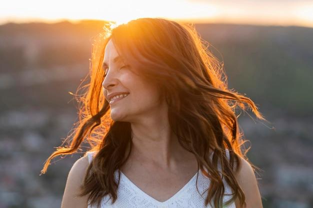 Vista frontal de la mujer posando al aire libre en la puesta del sol