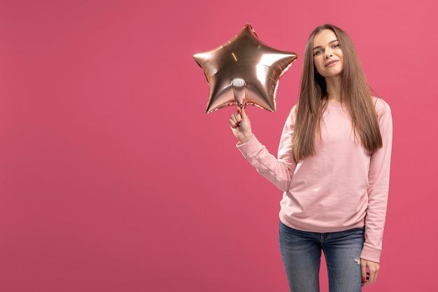 Vista frontal de la mujer posando con globo estrella