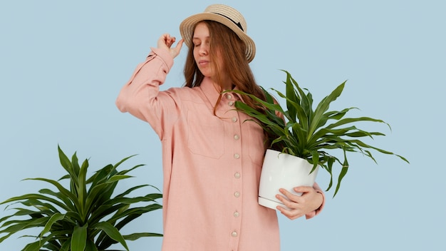 Vista frontal de la mujer posando con macetas de plantas