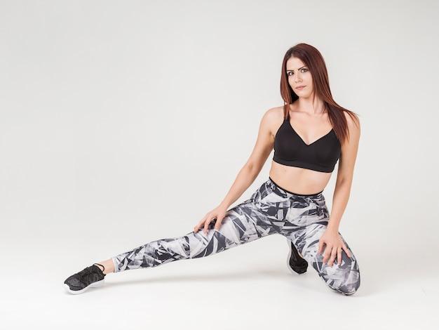 Vista frontal de la mujer posando mientras estira su pierna
