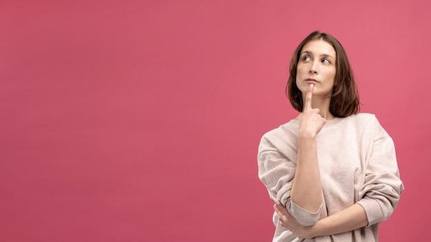 Vista frontal de la mujer posando mientras está pensando