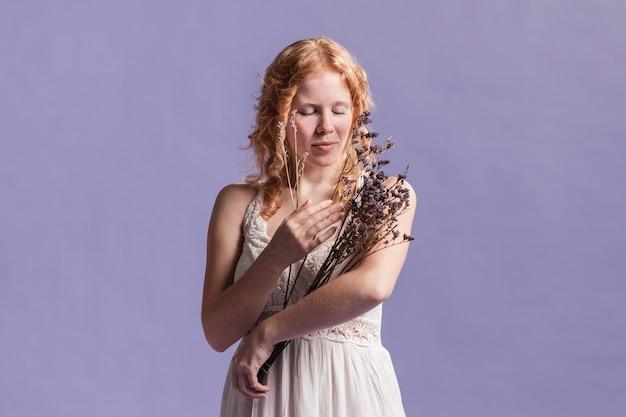 Vista frontal de la mujer posando mientras sostiene un ramo de lavanda