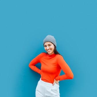 Vista frontal de la mujer posando sobre fondo azul