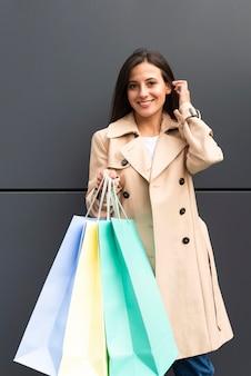 Vista frontal de la mujer posando sosteniendo bolsas de la compra.