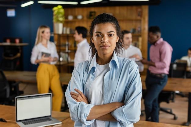 Vista frontal de la mujer posando en su oficina junto a la computadora portátil