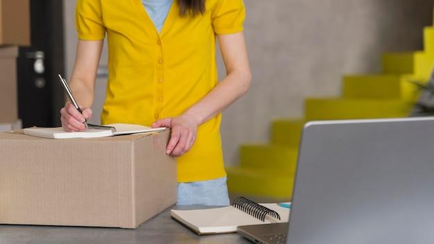 Vista frontal de la mujer preparando la caja para envío con laptop