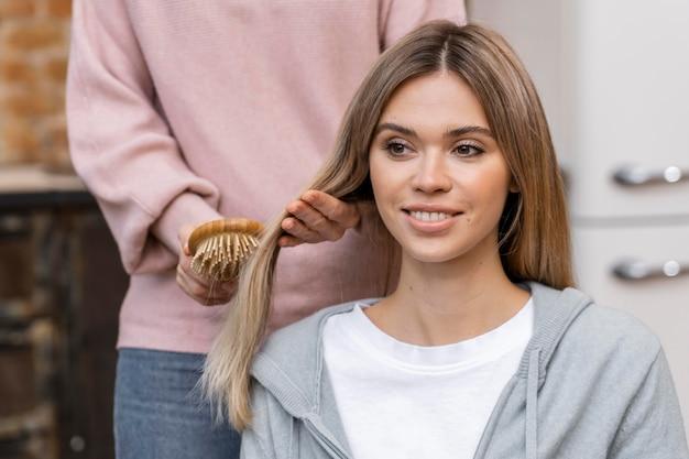 Vista frontal de la mujer que se cepilla el cabello en el salón