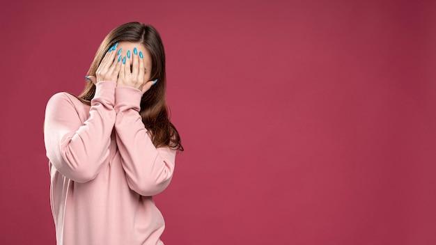 Vista frontal de la mujer que cubre su rostro con las manos