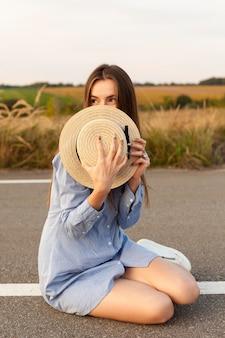 Vista frontal de la mujer que cubre su rostro con sombrero en medio de la carretera
