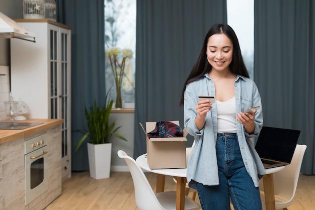 Vista frontal de la mujer que ordena en línea mientras mira la tarjeta de crédito