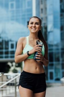 Vista frontal de la mujer que sostiene la botella de agua