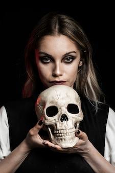 Vista frontal de la mujer que sostiene el cráneo humano
