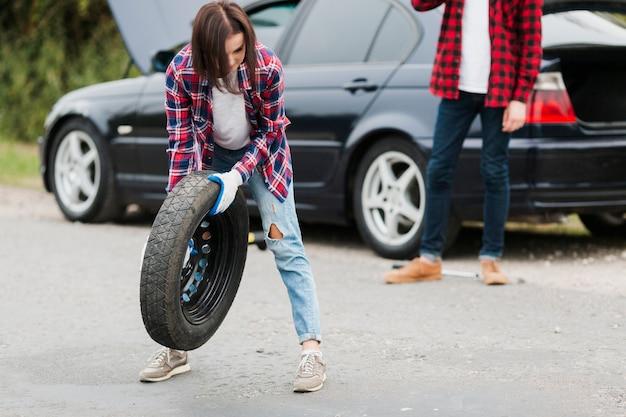Vista frontal de la mujer que sostiene el neumático