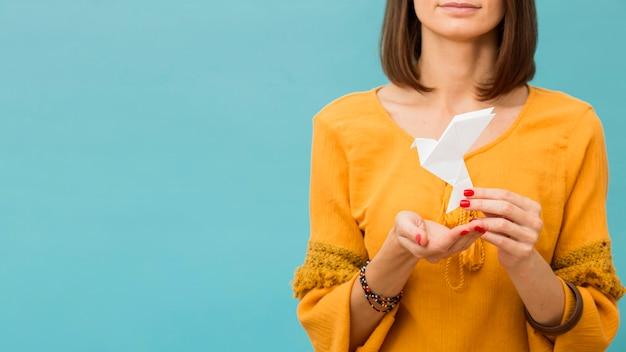 Vista frontal de la mujer que sostiene la paloma de papel con espacio de copia