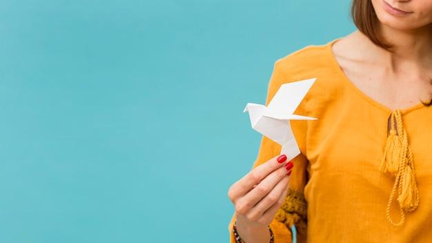 Vista frontal de la mujer que sostiene la paloma de papel