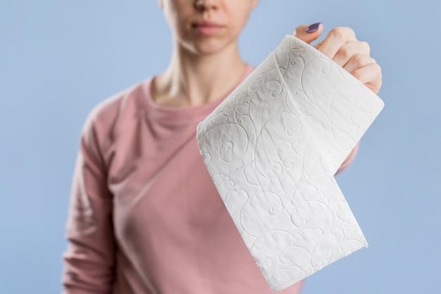 Vista frontal de la mujer que sostiene el rollo de papel higiénico
