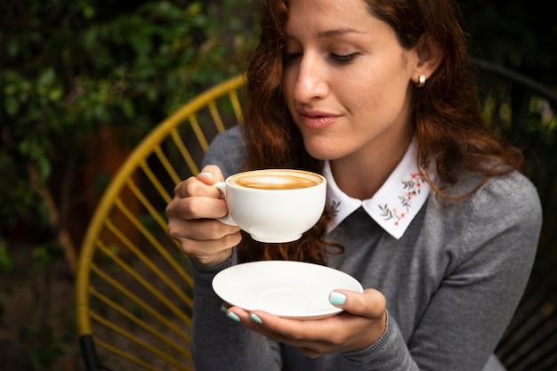 Vista frontal de la mujer que sostiene la taza de café